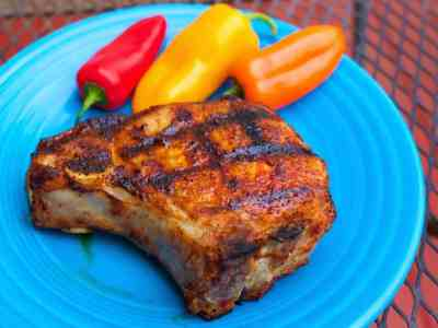 Grilled bone-in pork chop sprinkled with a spice rub on a blue plate with multicolored mini-peppers