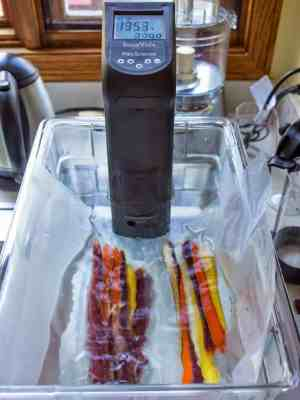 Vacuum sealed carrots in a water bath with a sous vide immersion circulator