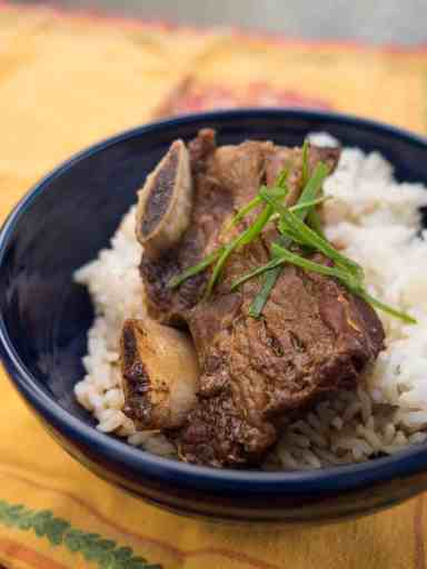 Braised short ribs on rice in a blue bowl, sprinkled with slivered scallions