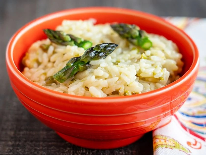 An orange bowl full of asparagus risotto with a napkin