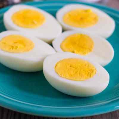 Hard-boiled egg halves on a teal plate