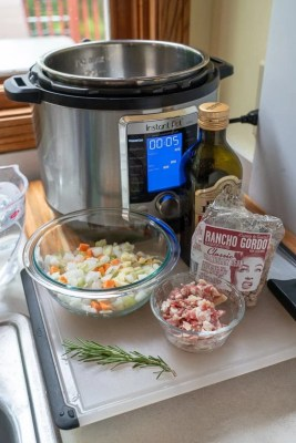 An instant pot behind a cutting board covered with ingredients, bowls of diced onions carrots, and celery, diced pancetta, a bag of cranberry beans, and a sprig of rosemary.
