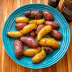 An overhead picture of a blue bowl full of multicolored fingerling potatoes, coated with herbs, with a jar of Herbes de Provence and a bottle of olive oil on the side