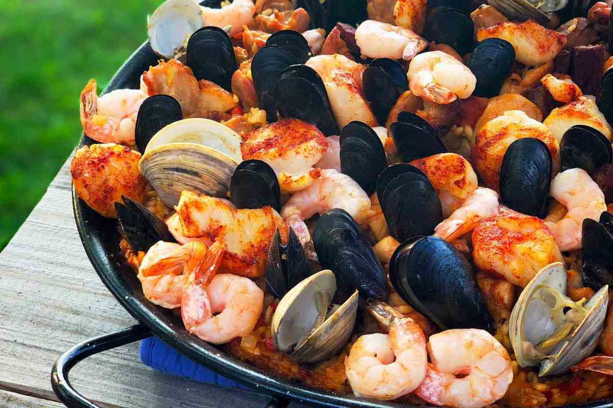 A black paella pan full of paella, bristling with shrimp, mussels, and clams, on a gray wooden table
