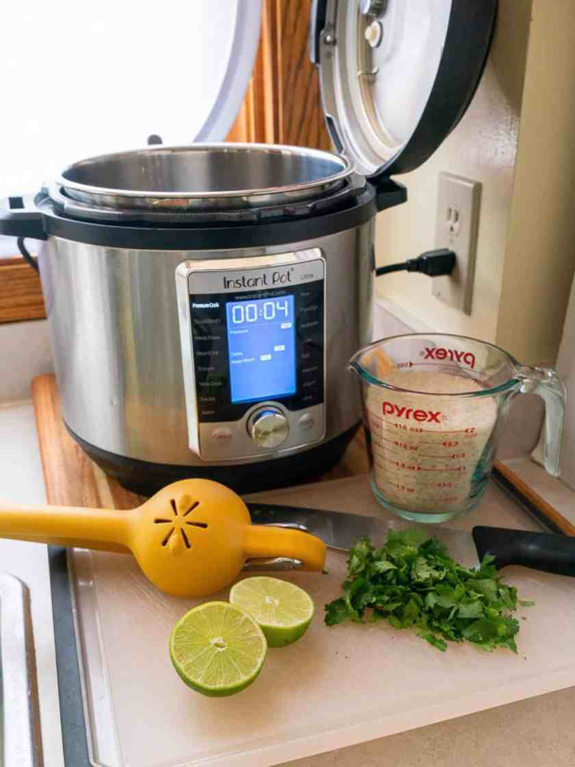 Instant Pot with rice, cilantro, limes, lemon squeezer, and chef's knife