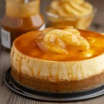Caramel Apple Cheesecake on a wood table, in front of a jar of caramel topping and a bowl of apples with the text Instant Pot Caramel Apple Cheesecake - DadCooksDinner
