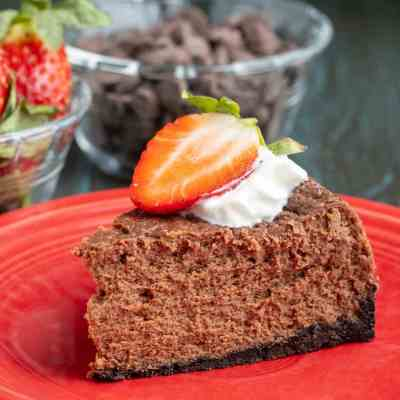 A piece of chocolate cheesecake, topped with whipped cream and a sliced strawberry, on a red plate, in front of a bowl of chocolate chips and strawberries.