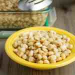 A yellow bowl of cooked hominy on a wooden tabletop, in front of a storage container of hominy
