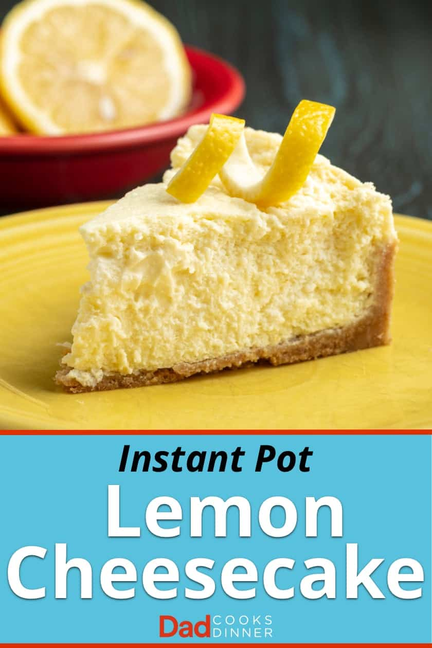 A slice of lemon cheesecake with a lemon twist on top, on a yellow plate, with a lemon in a red bowl in the background