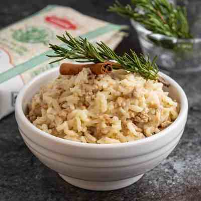A white bowl of risotto with pork and cinnamon, topped by a rosemary sprig and cinnamon stick, with a bag of rice and more rosemary in the background