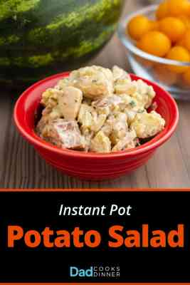 A red bowl of potato salad, on a wooden table, in front of a bowl of cherry tomatoes and a watermelon.