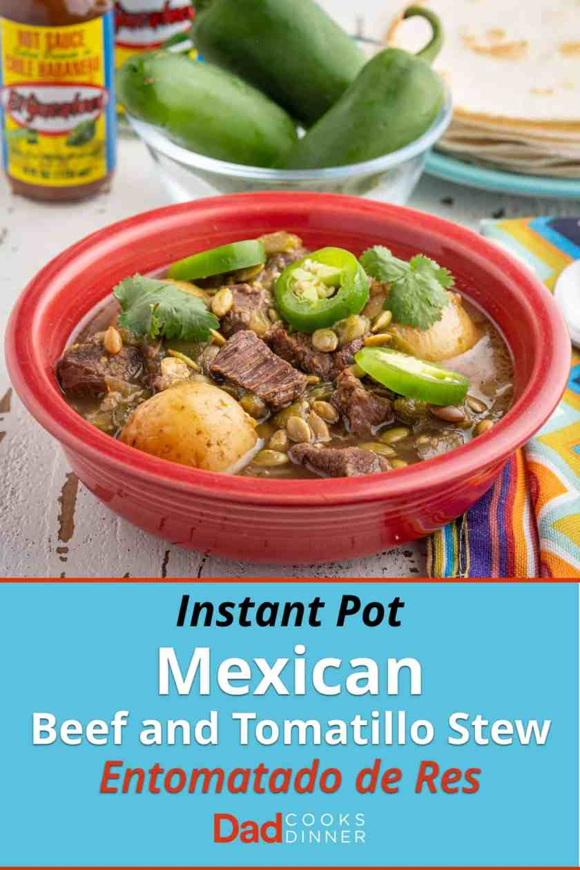 A red bowl of beef and tomatillo stew, with potatoes, sprinkled with sliced jalapeno, cilantro, and pepitas, with tortillas, jalapenos, and hot sauce in the background