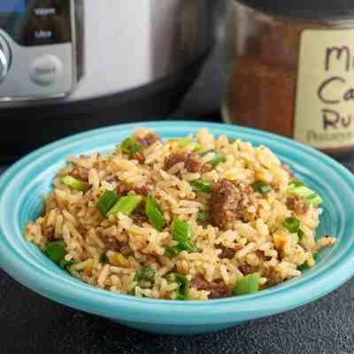 A bowl of Cajun dirty rice with an instant pot and a jar of Cajun seasoning in the background