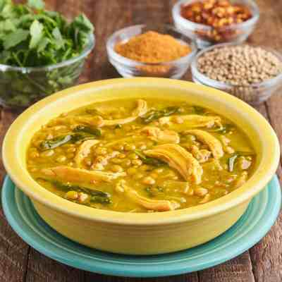 A yellow bowl of rotisserie chicken and lentil soup, with spices and herbs in the background