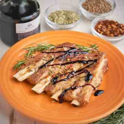 A slab of 4 ribs, sprinkled with herbs and drizzled with balsamic glaze, on an orange plate, with herbs and balsamic vinegar in the background.