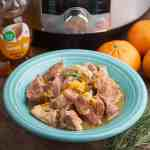 A blue bowl of braised pork, with orange zest and rosemary sprinkled on top, and an Instant Pot, oranges, honey bear, and rosemary sprigs in the background