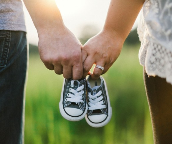 Image of a couple's hands holding a tiny pair of shoes