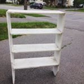 image of a broken white bookshelf rescued from the roadside garbage