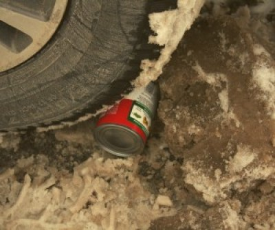 Image of a can of soup under a car tire