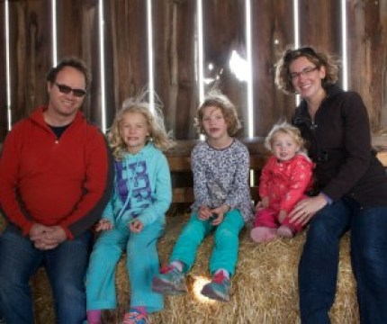 Image of a family sitting on hay bales 1 of 1000 families