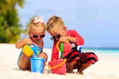 Dzieci bawią się na plaży, chłopak trzyma czerwoną konewkę a dziewczynka niebieską.