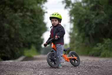 Chłopiec z kaskiem na rowerku biegowym.