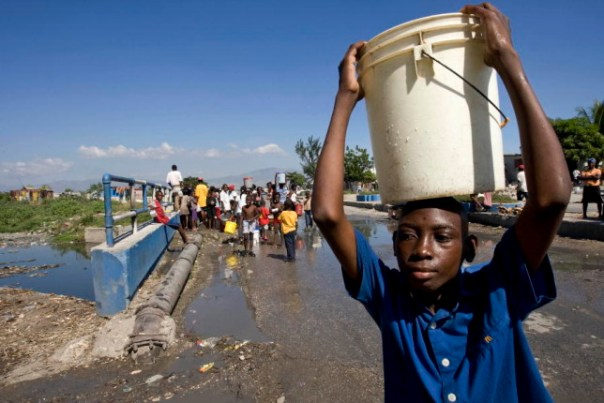 A boy in Cité Soleil carries away a hard-won bucket of water from a broken water pipe where many Haitians struggled for their share. The shanty town of Cité Soleil has been left with severely diminished water resources after a powerful earthquake rocked the area on 12 January. 15/Jan/2010. Cité Soleil, Haiti. UN Photo/Logan Abassi. www.un.org/av/photo/