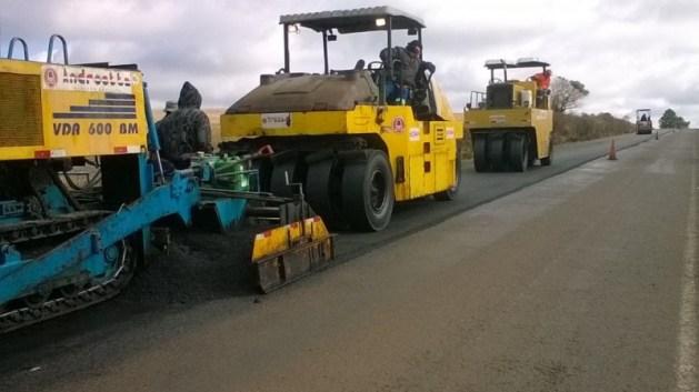 A foto mostra máquinas dirigidas por operários em uma obra de recuperação asfáltica, num trecho de rodovia em reta