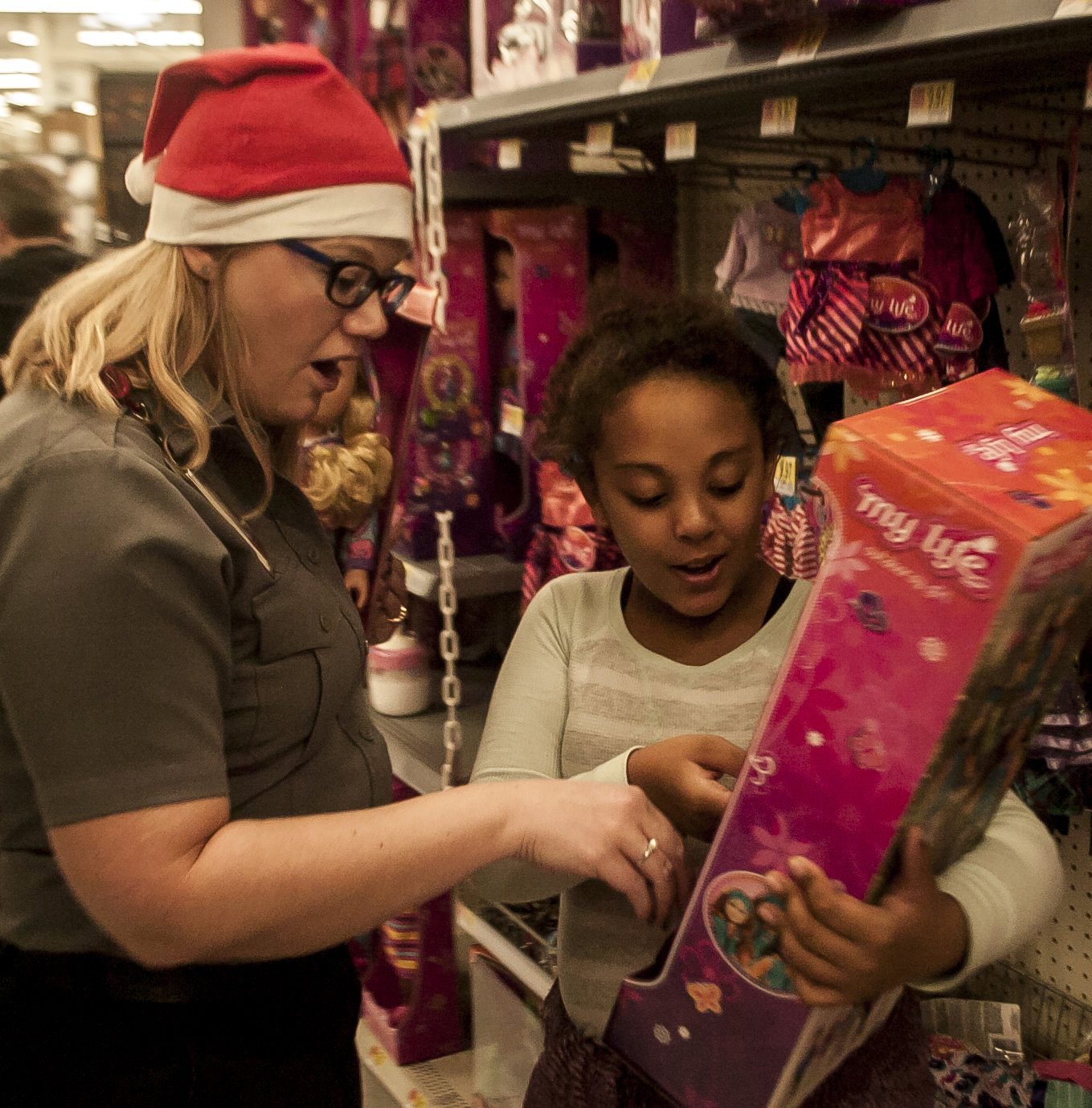 MetroAtlanta's Amber Barber, left, helps Avana Jewell pick out a Christmas present Saturday at Walmart during the Shop with a Hero event.