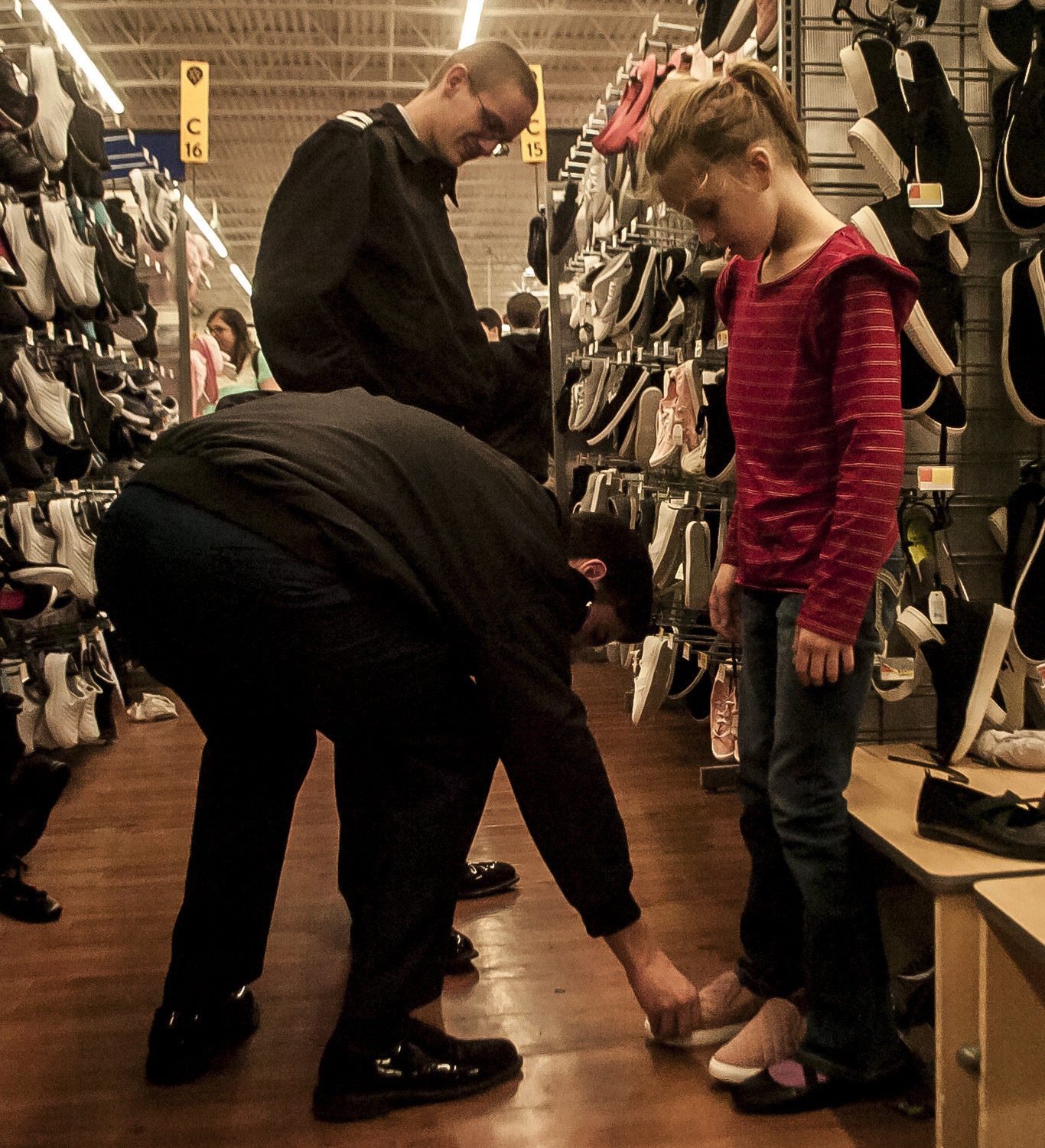 Kyleigh Garrett gets fitted for new shoes by Cass High JROTC members Aaron Whitlock, front, and Christopher Bilodeau at Saturday's Shop with a Hero event in Cartersville.