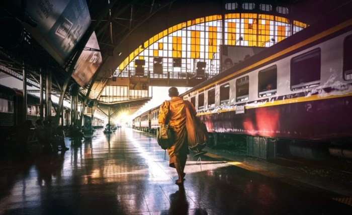A Buddhist monk walks through Bangkok's old train station to catch his departure.