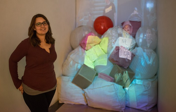 Ana Maria Gallo stands with her piece entitled Pillars of Modern America: a collection of video footage projected onto sewn fabrics.