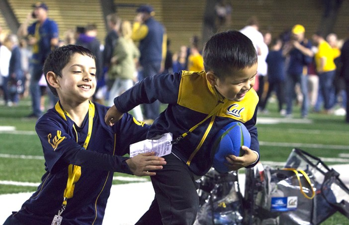 A pair of young fans play their own game of football after storming the field. KAREN CHOW/SENIOR STAFF