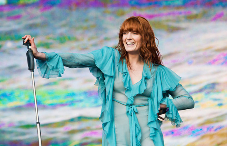 Florence Welch holding onto a microphone stand on stage