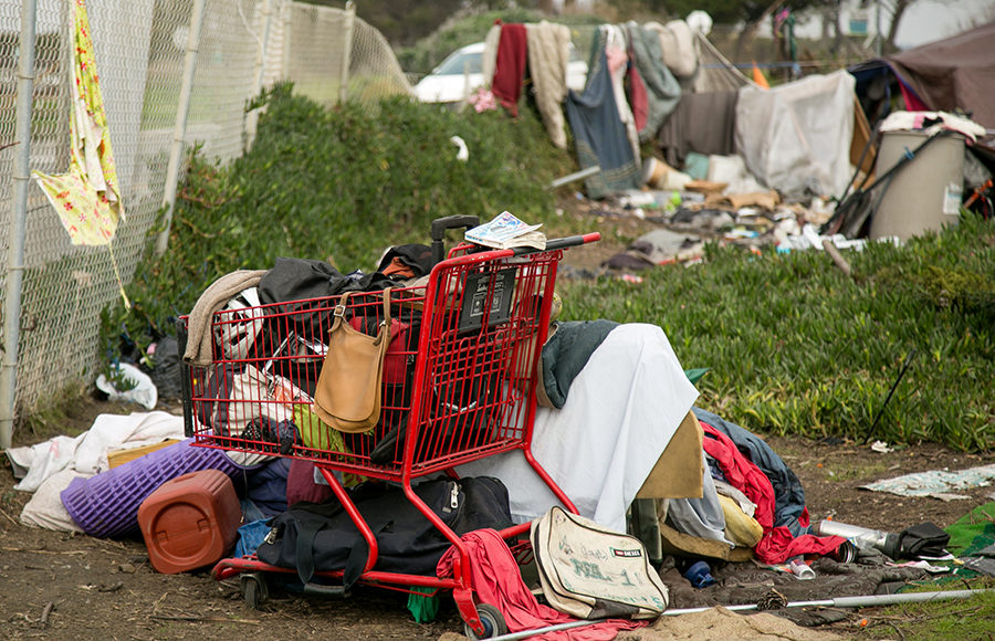 A red shopping cart rests alone in the middle of a field, overflowing with random items such as a purse, a bicycle helmet, and clothes, alongside a metal fence. Under the shopping cart an in the background there are more random items and clothes.