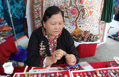A woman sitting on a table holding rings that she sells