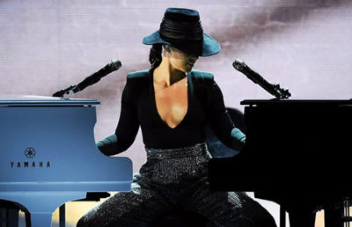 Woman sits in between two pianos, playing them with each hand. She looks down to her left. Her black hat covers her eyes.