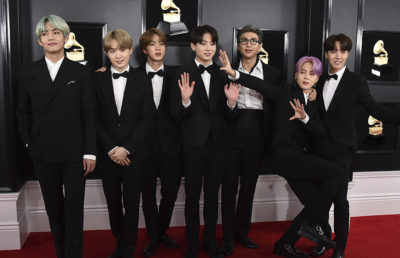 Boy band of seven members poses on red carpet.