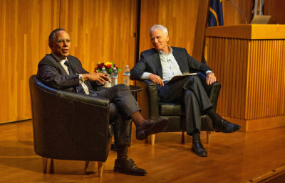 Two men sit on chairs on a stage, one of them speaking to the audience, the other looking at the man who is speaking.