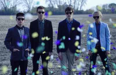 4 people standing with suit jackets and sunglasses with confetti flying in front of the camera.