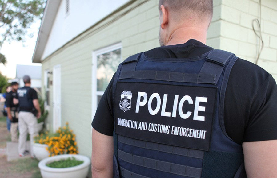 An ICE police officer looks towards a scene in the background where more officers are standing outside a house.