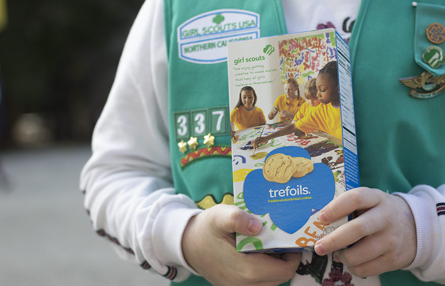 Young girl dressed in Girl Scout uniform holds a box of cookies.