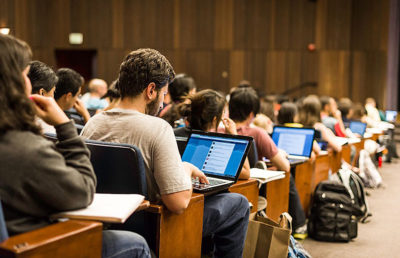 Students sit at large lecture hall, all of them looking at their computer or notebook.