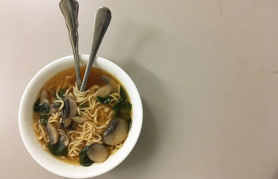 A bowl of noodles in miso soup with mushrooms.