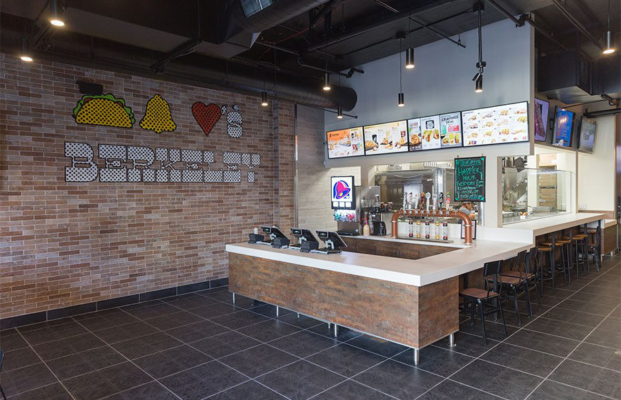 The inside of an empty Taco Bell restaurant. The resisters, menu, and a few sitting options are pictured.