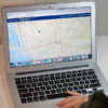 A person uses Google Maps on their Macbook Air laptop.