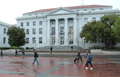 Students walk past Sproul Hall on a gloomy day.