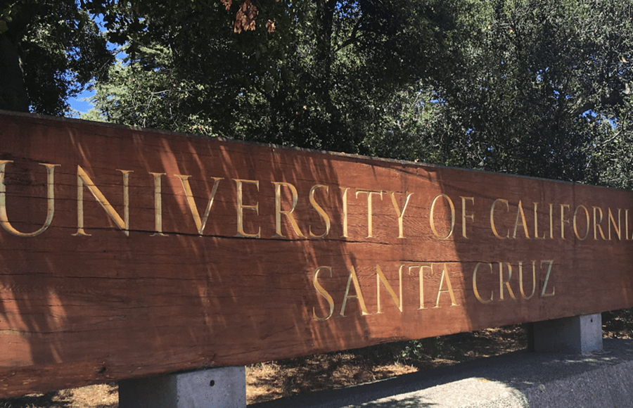 "A wooden sign in the forest reads ""University of California Santa Cruz""."