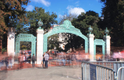 A long exposure photo of a large crowd of people walking past Sather Gate so that they appear to be blurry at how fast they are walking