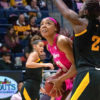 A basketball player has the ball in her hand and tries to get around a player from the opponent team who is attempting to block her.